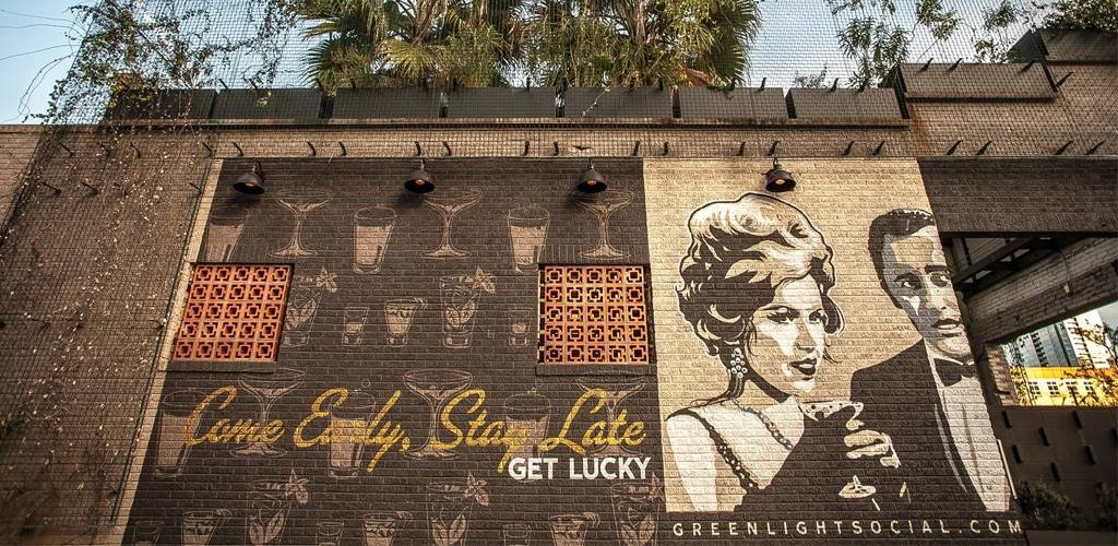 Brick Wall outside Green Light Social in Austin, TX that says Come Early, Stay Late, Get Lucky